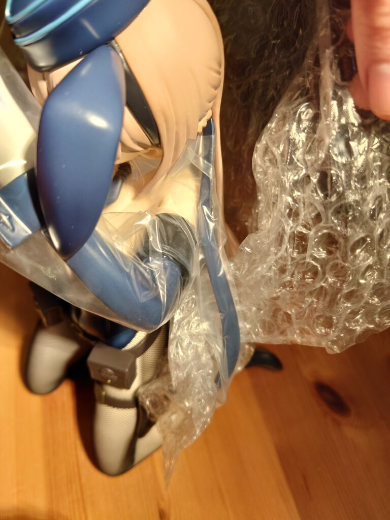 View of the bubble wrap and plastic protecting the back of her hair, her arm, and her long hair ribbon.